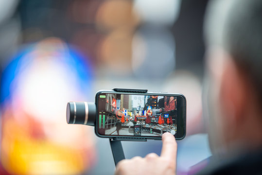 Tourist taking pictures of Times Square with mobile device and stabilizer