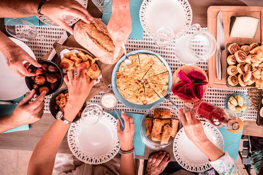 Top view of colorful table full of mixed culture food and hands and people eating and having fun in friendship together - lunch celebration for caucasian friends eating and drinking