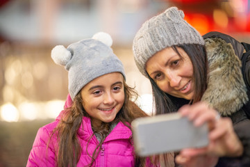 Young girl with mother happy in the city at night making selfie