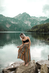 Young woman relaxing in the nature under the rain lake and mountains background