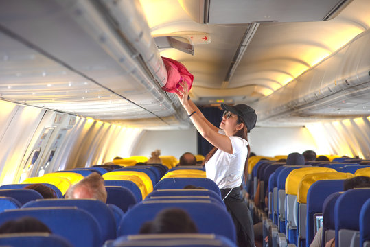 woman passenger traveler on boarding aircraft looking for empty overhead locker for luggage keep in safe on the flight