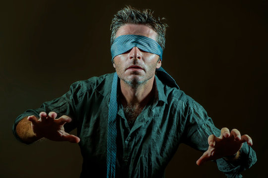 young lost and confused man blindfolded with necktie playing internet trend dangerous viral challenge with eyes blind isolated on black background