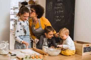 we have so much fun when baking. senior woman with her grandchildren baking in kitchen