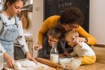 making something sweet. senior woman with her grandchildren baking in kitchen