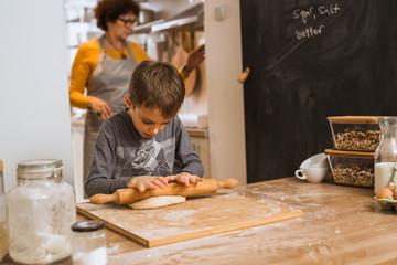he is grandmother's little helper. little boy helping his grandmother baking in kitchen