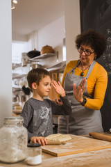 give me high five. little boy and his grandmother baking together in kitchen.
