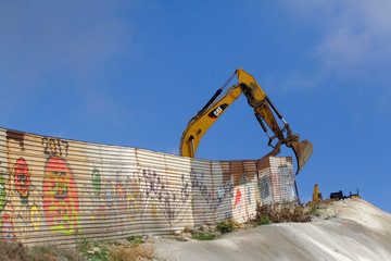 U.S. workers use machinery to replace the metal sheets of the border fence between the U.S. and Mexico, as seen from Tijuana