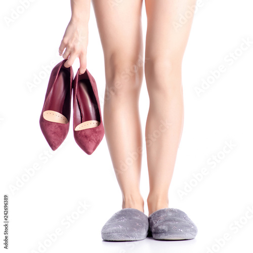 446a4fa73 beautiful female legs takes off her shoes and puts on slippers on white  background isolation