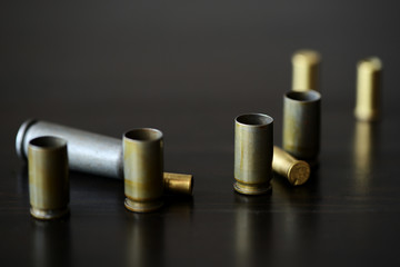Empty old bullet cartridges on a dark background close up