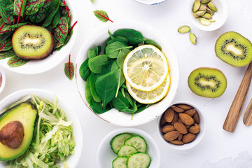 Green ingredients for spring detox salads: spinach, sorrel with red veins, cucumbers, radishes, iceberg lettuce, green peas, avocados, lemon, microgreen, yellow tomatoes on a white background with