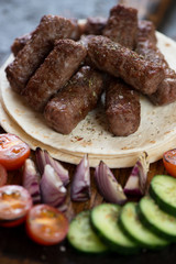 Barbecued balkan cevapi or skinless beef sausages on tortilla flatbread with vegetables, closeup