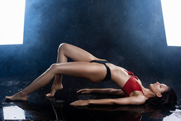 A beautiful sexy wet leggy brunette girl, dressed in black panties and a red bra, sits on the floor and sensually flexes under raindrops in theatrical smoke. Copy space.