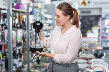 Woman  housewife looking electric kettle in kitchen appliances section