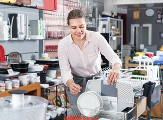 Female buyer trying kitchen rack in the tableware store