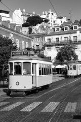 Black and white picture of a vintage tram on old streets of Lisbon, Alfama, Portugal, popular touristic attraction and destination.
