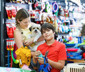 Happy teen boy with mother visiting pet shop in search of access