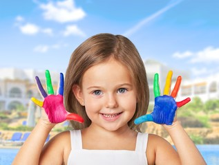 Cute little girl with colorful painted hands on  background
