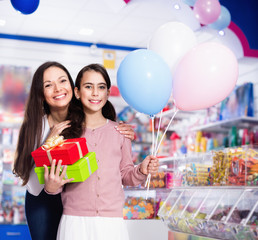 Portrait of mother and daughter holding gifts and balloons in store