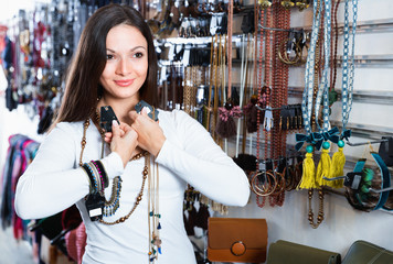 Cheerful young woman choosing  different pendants and bracelets in the market