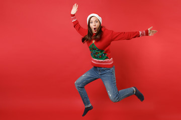 Shocked young Santa girl keeping mouth wide open, looking surprised jumping spreading hands, legs isolated on red background. Happy New Year 2019 celebration holiday party concept. Mock up copy space.