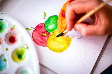 Woman hand with paint brush drawing apples and pie.