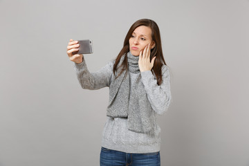 Sad young woman in sweater, scarf putting hand on cheek, doing selfie shot on mobile phone making video call isolated on grey background. Healthy fashion lifestyle people emotions cold season concept.