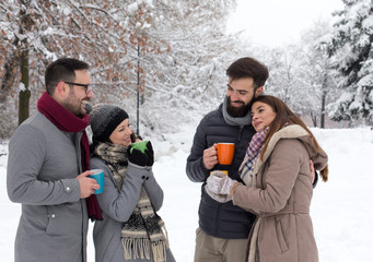 Frineds with hot cups on snow