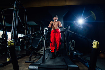 Shirtless young male holding ropes and running on treadmill while exercising in dark gym
