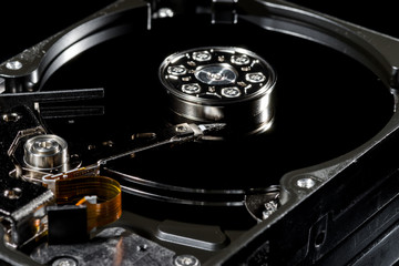 Disassembled and opened hard disk drive, inside view with reflections, isolated on black