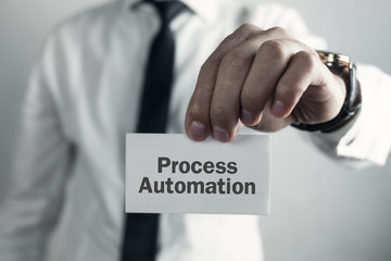 Businessman showing word Process Automation on business card.