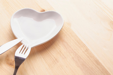 Red heart on a white plate in the form of a heart on a wooden background with a fork and knife
