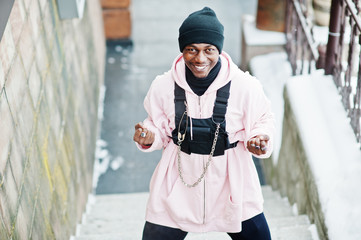 Stylish urban style african american man in pink hoodie posed at winter day and boxing hands.