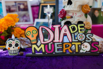 Dia de los Muertos/Day of the Dead decoration with sugar skulls, roses and ofrenda/altar in the background