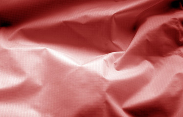 Crumpled transparent plastic surface in red color.