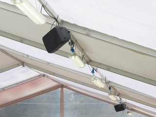 speakers and neon lights on the ceiling of  tensile structure