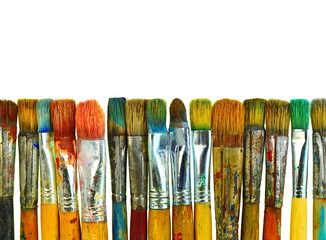 Various dirty paint brushes. Paints and brushes isolated on white.