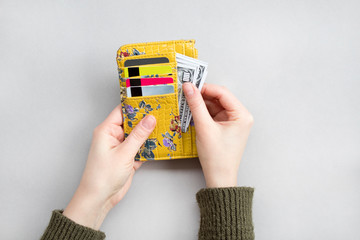 Female hand holding wallet with dollar and bank cards on the grey background.
