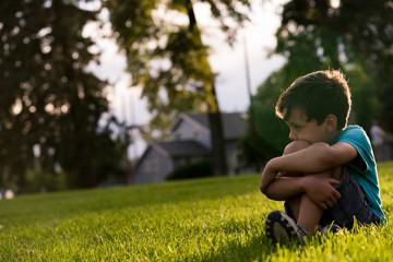 Sad boy sitting on grass