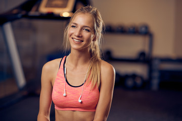 Close up of smiling blonde Caucasian woman with ponytail in the gym. Around neck earphones. Healthy lifestyle concept.