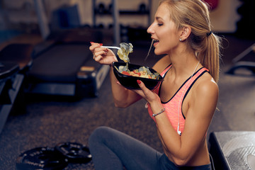 Side view of woman eating healthy food while sitting in a gym. Healthy lifestyle concept.