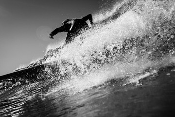 Rear view of surfer surfing in sea against sky