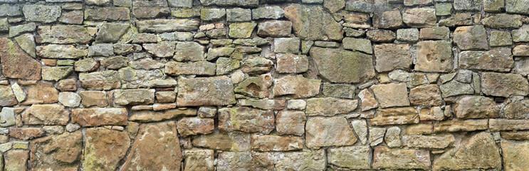 Panorama einer sehr alten, groben Natursteinmauer aus unterschiedlich großen Steinen