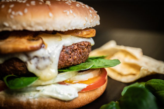 Hamburger vegetarian burger with falafel and vegetables salad tomato champignon and cheese tofu cheese all vegan food with nachos in blurred background