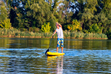 Happy man is training on a SUP board on large river