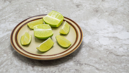 small plate with ripe green lime sections and juicy lime wedges on a gray marble counter with copy space
