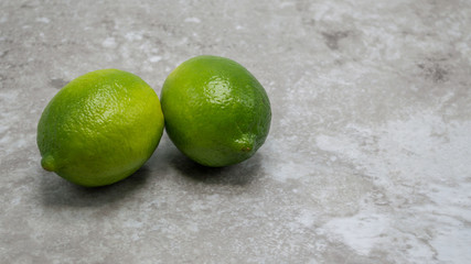 two ripe green limes on a gray marble counter with copy space