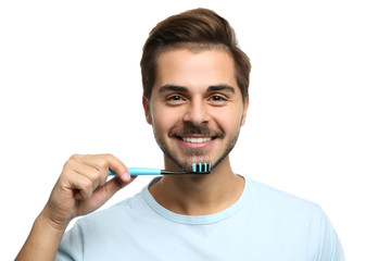Portrait of young man with toothbrush on white background