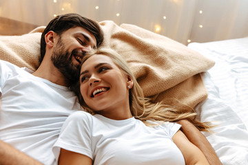 Obraz Love. Fun. Emotions. Young couple are laughing while lying together on the bed - fototapety do salonu