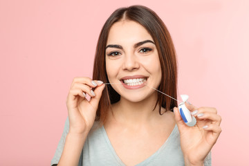 Young woman flossing teeth on color background