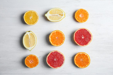Different citrus fruits on wooden background, flat lay